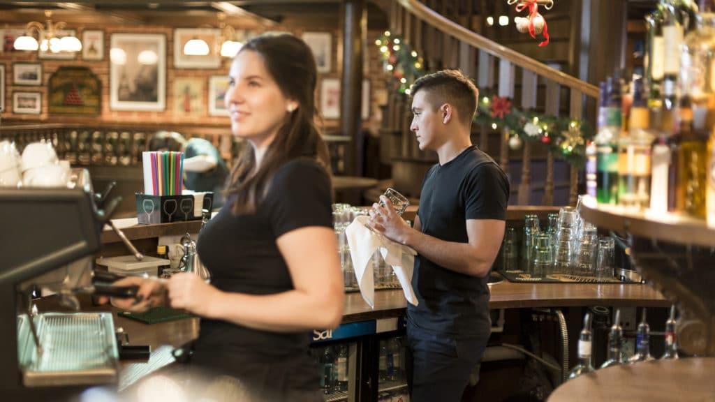 Personnes derrière un bar effectuant un service.