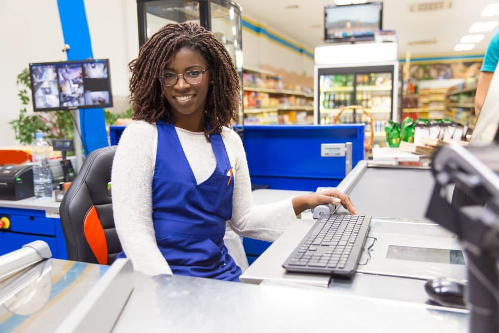 Femme souriante derrière la caisse d'un super marché.