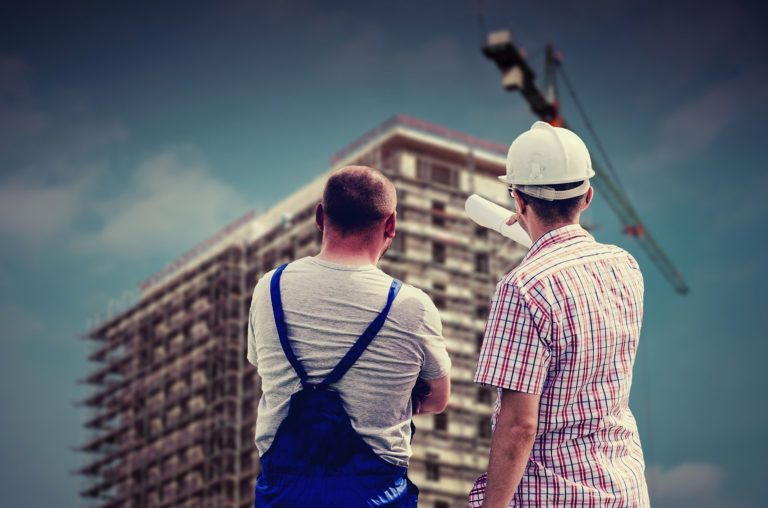 Contre-Maître et ouvrier discutant devant un immeuble en construction.